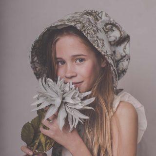 niña con gorro de color verde musgo mirando a cámara y con flores azules en la cara