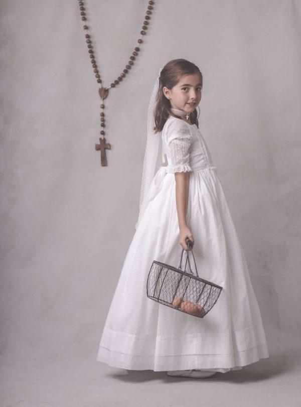niña de comunion con cesta de metal en mano