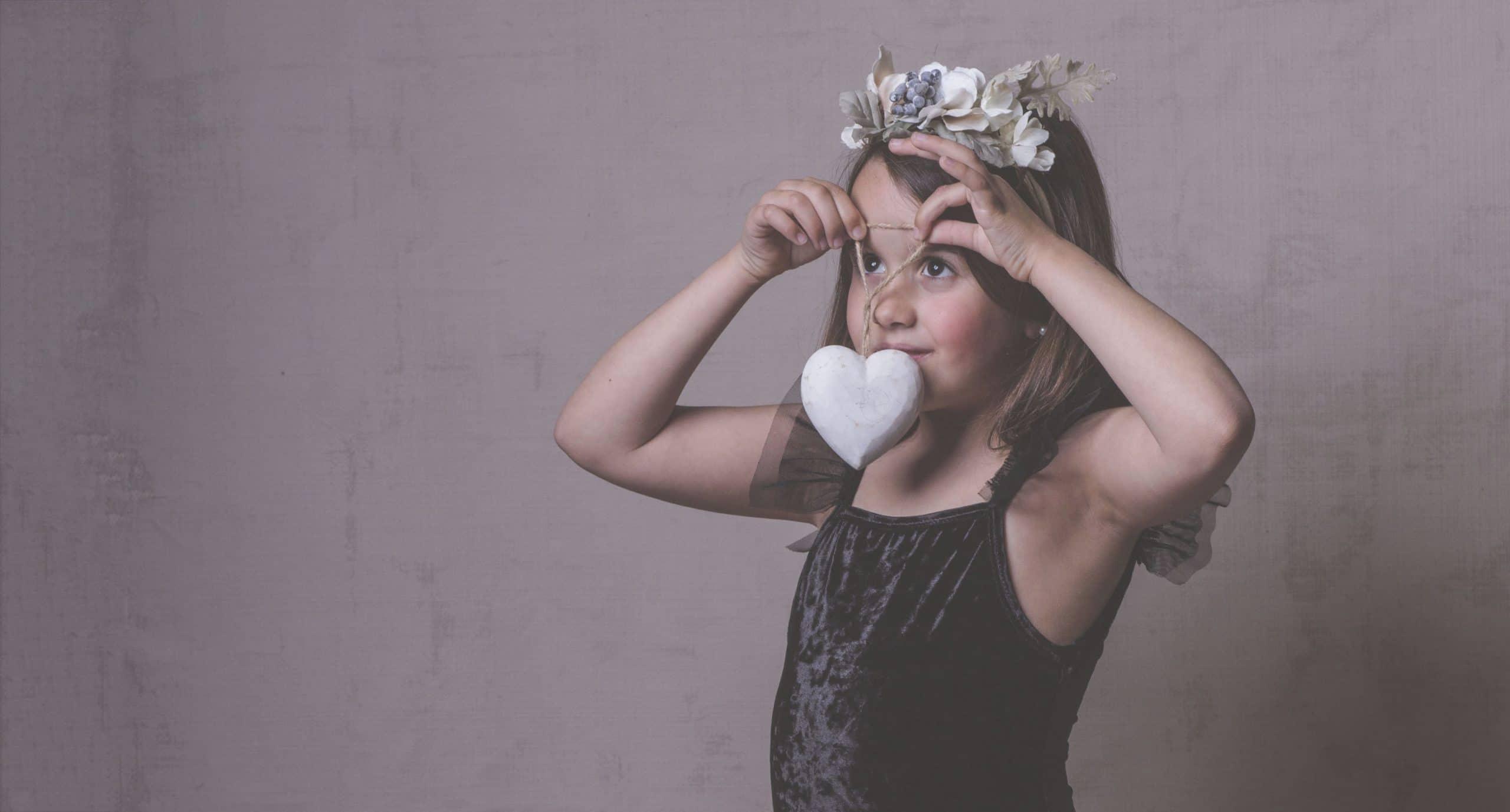 niña con body negro flores en el pelo y cocaron de madera blanco