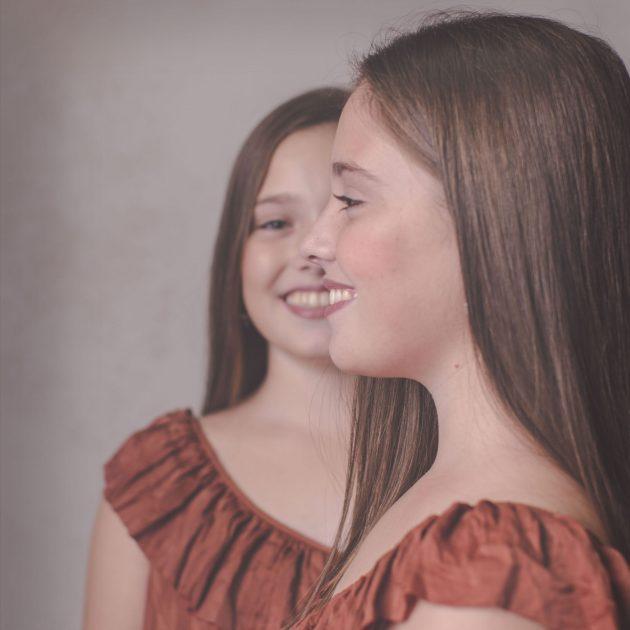 niñas gemelas una de perfil y otra de frente vestido naranja de verano